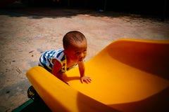 Bambino sullo scorrevole del campo da giuoco immagini stock libere da diritti