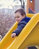 Bambino sullo scorrevole del campo da giuoco Immagine Stock