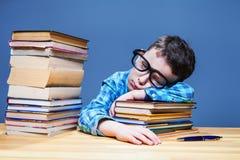 Bambino sveglio addormentato allo scrittorio nella biblioteca di scuola Fotografia Stock