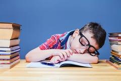 Bambino sveglio addormentato allo scrittorio nella biblioteca di scuola Fotografie Stock Libere da Diritti