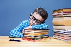 Bambino sveglio addormentato allo scrittorio nella biblioteca di scuola Immagine Stock Libera da Diritti