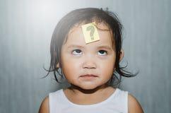 Bambino sveglio asiatico che esamina il punto interrogativo sulla sua fronte con il fronte divertente immagine stock libera da diritti