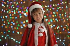 Bambino sveglio in cappello di Santa sul fondo vago delle luci Celebrazione di natale Fotografia Stock