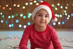 Bambino sveglio in cappello di Santa sul fondo vago delle luci Celebrazione di natale Immagini Stock