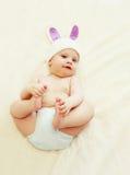 Bambino sveglio in cappello tricottato con le orecchie di coniglio che si trovano sulla casa del letto Fotografia Stock Libera da Diritti