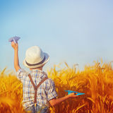 Bambino sveglio che cammina nel giacimento dorato del grano un giorno di estate soleggiato quadrato Fotografia Stock