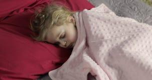 Bambino sveglio che dorme sul letto a casa Bambina che dorme alla luce di mattina archivi video