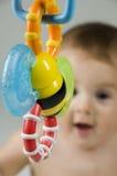 Bambino sveglio che esamina giocattolo Fotografia Stock Libera da Diritti