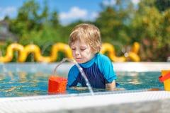 Bambino sveglio che gioca con acqua dalla piscina all'aperto Fotografie Stock Libere da Diritti