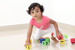 Bambino sveglio che gioca con i cubi di alfabeto della schiuma immagine stock libera da diritti