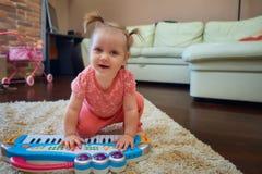 Bambino sveglio che gioca con il piano del giocattolo fotografie stock libere da diritti