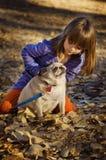 Bambino sveglio che gioca con l'autunno del cane del pug fotografia stock