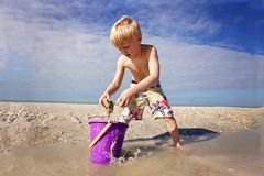 Bambino sveglio che gioca con la sabbia in un secchio alla spiaggia dall'oceano immagini stock