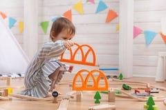 Bambino sveglio che gioca con la strada ferroviaria del giocattolo a casa immagini stock libere da diritti