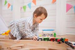 Bambino sveglio che gioca con la strada ferroviaria del giocattolo a casa fotografia stock