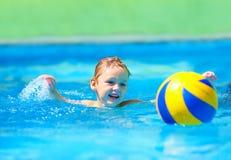 Bambino sveglio che gioca i giochi dello sport acquatico in stagno Fotografie Stock Libere da Diritti