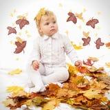 Bambino sveglio che gioca le foglie di autunno del Th Immagini Stock