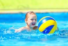 Bambino sveglio che gioca nei giochi dello sport acquatico in stagno fotografia stock