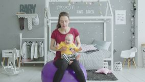 Bambino sveglio che gode dell'allenamento della forma fisica della mamma sulla palla stock footage