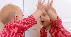 Bambino sveglio che guarda in specchio stock footage