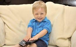 Bambino sveglio che guarda TV, sedentesi nella presidenza Fotografia Stock