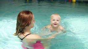 Bambino sveglio che ha lezione di nuoto con sua madre Famiglia in buona salute che insegna al loro bambino a nuotare nella piscin archivi video