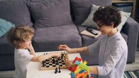 Bambino sveglio che impara giocare scacchi e che si diverte con la giovane madre allegra video d archivio