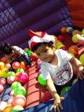 Bambino sveglio che indossa il cappuccio rosso di Santa che si siede nelle palle variopinte Fotografia Stock Libera da Diritti