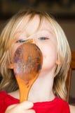 Bambino sveglio che lecca cioccolato fuori da un cucchiaio di legno Fotografia Stock
