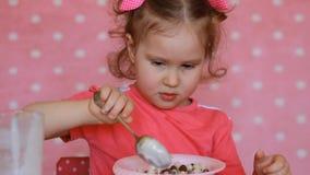 Bambino sveglio che mangia i cereali Bambina che mangia cereale da prima colazione con sorridere del yogurt della bevanda a base  stock footage