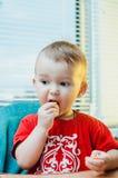 Bambino sveglio che mangia mandarino fotografia stock libera da diritti
