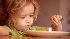 Bambino sveglio che mangia prima colazione a casa Ritratto di piccolo neonato di risata dolce con capelli biondi che mangia dal p video d archivio