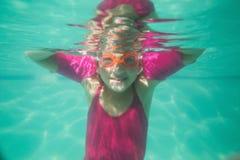 Bambino sveglio che posa underwater nello stagno Immagini Stock