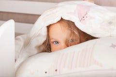 Bambino sveglio che si nasconde sotto la coperta fotografia stock libera da diritti