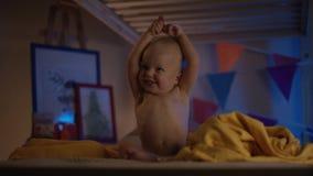 Bambino sveglio che si siede appena al cattivo ed applauso felice ai suoi genitori ed a sorridere molto archivi video