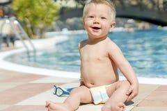 Bambino sveglio che si siede dalla piscina nella località di soggiorno immagine stock