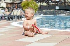 Bambino sveglio che si siede dalla piscina nella località di soggiorno immagine stock libera da diritti