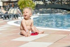 Bambino sveglio che si siede dalla piscina nella località di soggiorno fotografia stock