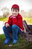 Bambino sveglio che si siede sul tronco Fotografia Stock
