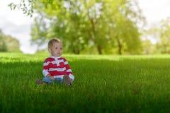 Bambino sveglio che si siede sull'erba verde Fotografie Stock Libere da Diritti