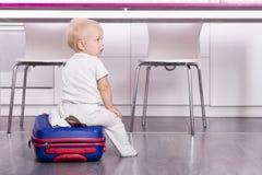 Bambino sveglio che si siede sulla valigia e che esamina macchina fotografica Neonato divertente che va vacation Immagini Stock
