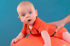 Bambino sveglio che si trova sul fitball arancio sui precedenti blu Co Immagine Stock