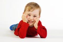 Bambino sveglio che si trova sul pavimento fotografia stock