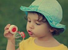 Bambino sveglio che soffia grande bolla. immagine stock