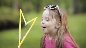 Bambino sveglio che soffia una bolla in parco stock footage