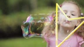 Bambino sveglio che soffia una bolla in parco video d archivio