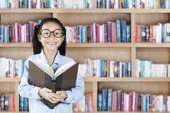 Bambino sveglio che sorride con il libro in biblioteca Immagini Stock Libere da Diritti