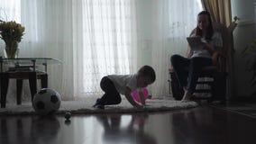 Bambino sveglio che striscia sul pavimento su tappeto lanuginoso che gioca con le palle ed il pallone mentre la sua giovane madre video d archivio