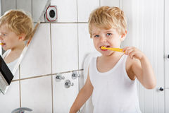 Bambino sveglio con gli occhi azzurri ed i capelli biondi che puliscono i suoi denti fotografia stock libera da diritti