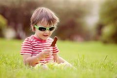 Bambino sveglio con gli occhiali da sole, mangianti la lecca-lecca del cioccolato Fotografia Stock